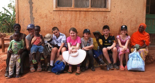 Highfield pupils with a Ugandan family outisde their home